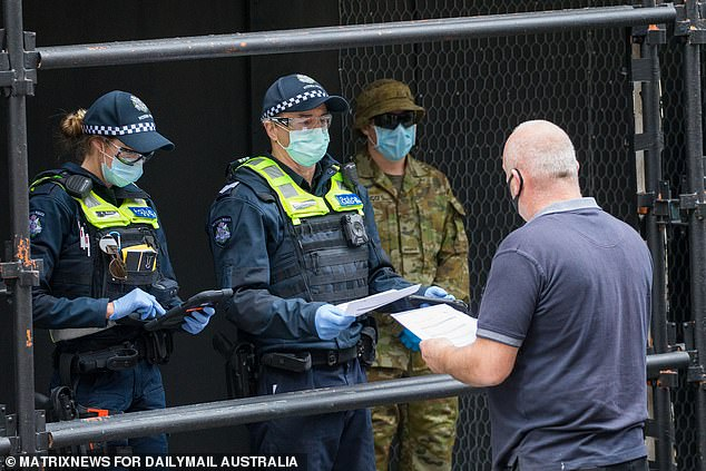 Police check the permit papers of a worker on day 1 of the full stage 4 lockdown restrictions