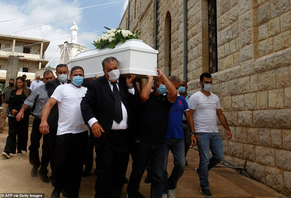 The explosion has 137 people dead, at least 5,000 people wounded and 300,000 homeless as dozens of funerals begin across the city. Pictured:Men carry the coffin of Nicole Helou, 25, a Lebanese woman killed in the blast on Tuesday
