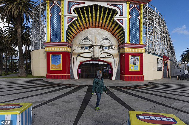 A Melburnian in a face mask walks in front of closed Luna Park in St Kilda during Melbourne's lockdown (pictured on Wednesday)