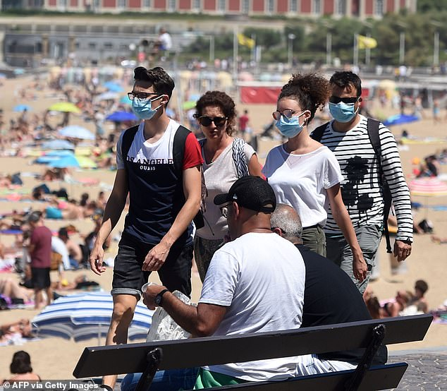 People wearing face masks walk along the beach at the French resort of Biarritz on Monday