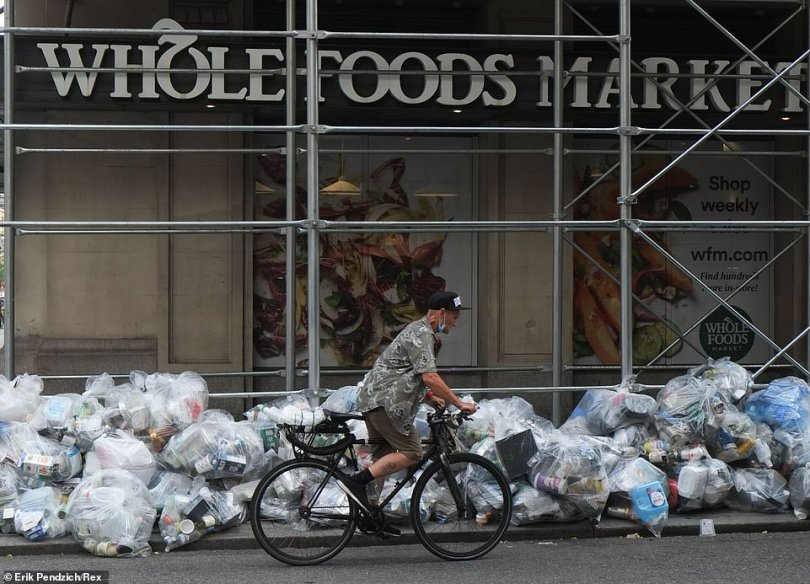 Midtown Manhattan: New York City slashed $106 million to the sanitation department's budget to get costs under control. Bags of garbage litter the sidewalk outside a Whole Foods Market on July 30