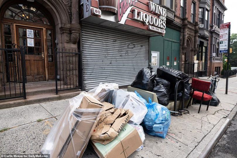 Flatbush, Brooklyn: Piles of garbage and recycling are pictured overflowing on the sidewalk outside buildings on Friday