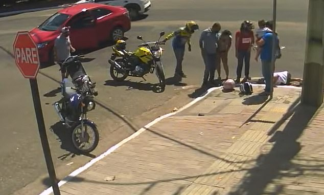 Bystanders stand near the manhole where Mayara dos Santos fell through after the scooter she was riding was hit by a car Wednesday inParagominas, a city in the northern Brazilian state of Pará