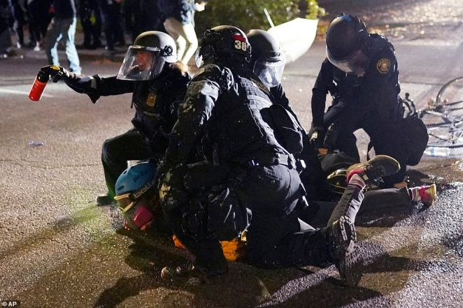 Police in Portland, Oregon, are pictured pinning down a masked protester overnight Friday in the 72nd night of violence