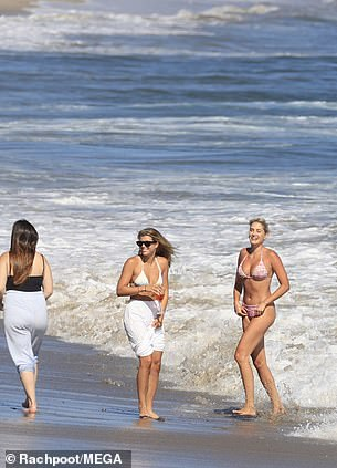 Fun in the surf: She held her loose white pants up to avoid getting them wet