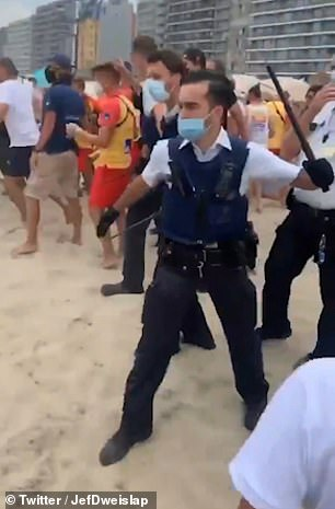 Police officers hold batons as they were called into action