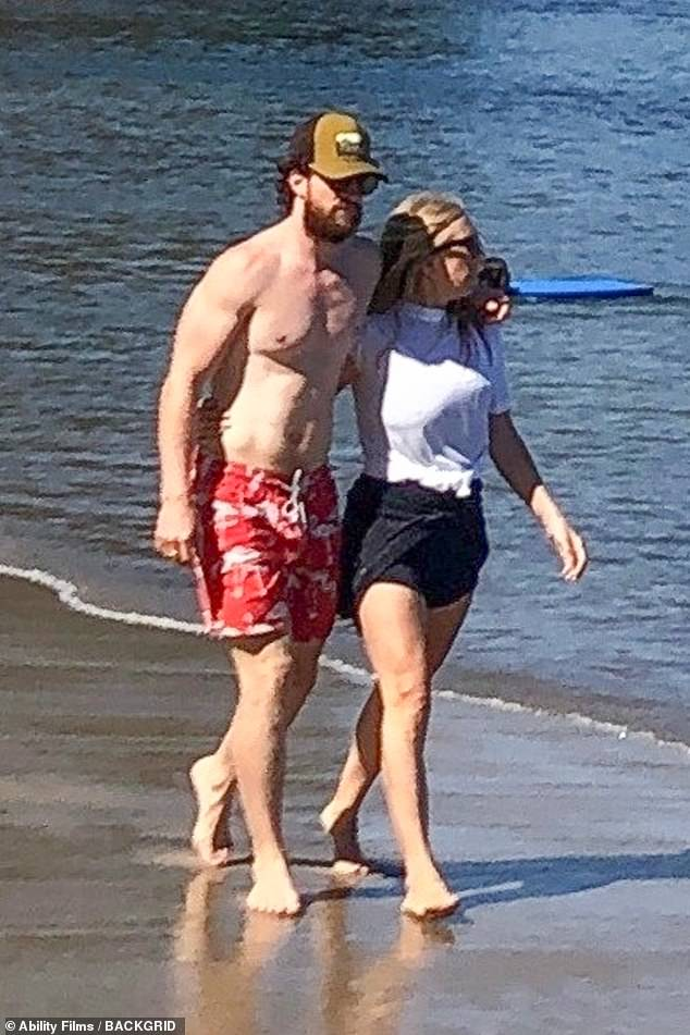 Adorable: The pair walked barefoot along the sand as Aaron draped his arm over Sam's shoulder who, in turn, had her hand wrapped around his waist