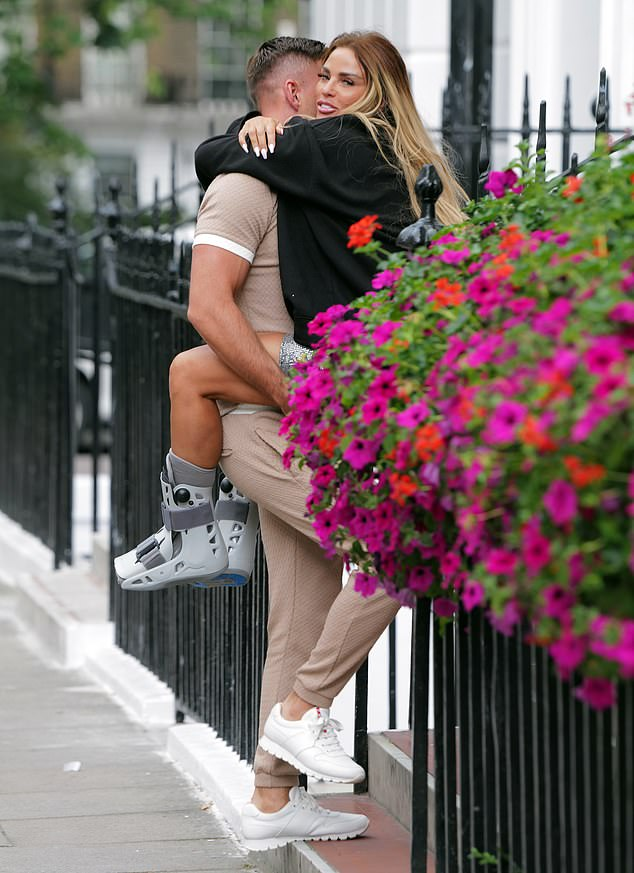 Helping hand:Katie Price was needing the assistance of her hunky boyfriend Carl Woods as he carried her into an appointment on Sunday