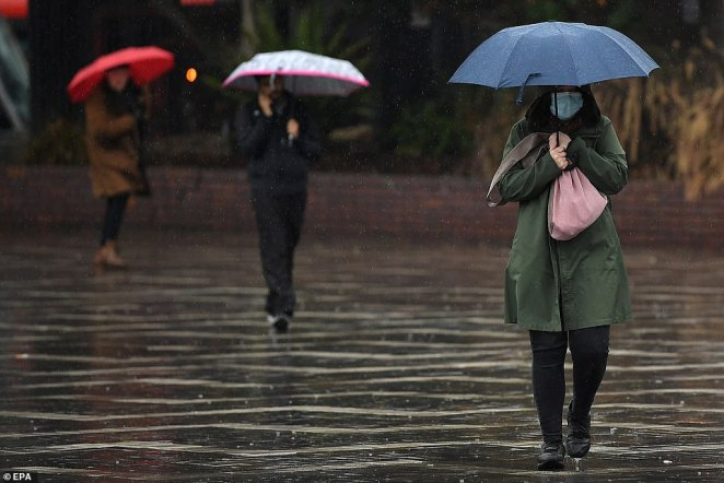 A woman wearing a face mask walks through a soaked Circular Quay in Sydney