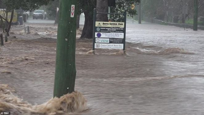 A telegraph pole is seen with water rushing past it in Berry as the South Coast town suffers horrific rainfall
