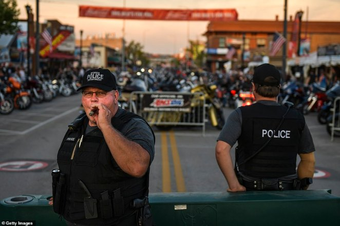 Sturgis police officer smokes a cigar as he stands watch on Main Street during the 80th Annual Sturgis Motorcycle Rally Friday