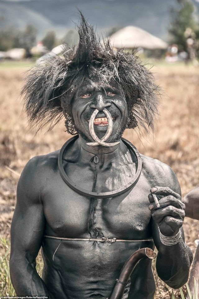 Holding a cigarette, this smiling Dani leader is covered in silver body paint made ash and pig fat. A pig rib nose ring completes his silvery look
