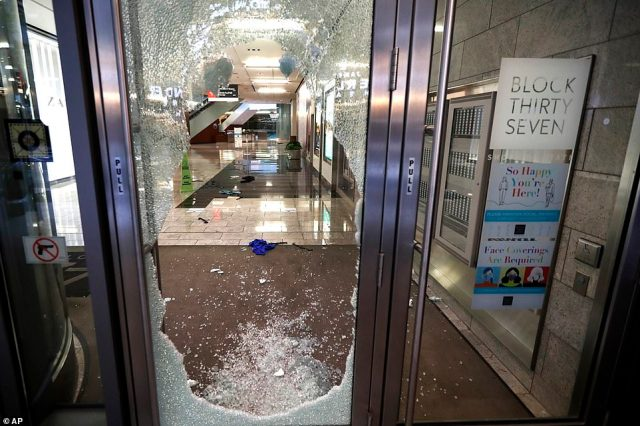 A door to the Block 37 retail building is shattered Monday, Aug. 10, 2020, after vandals struck overnight in Chicago's famed Loop