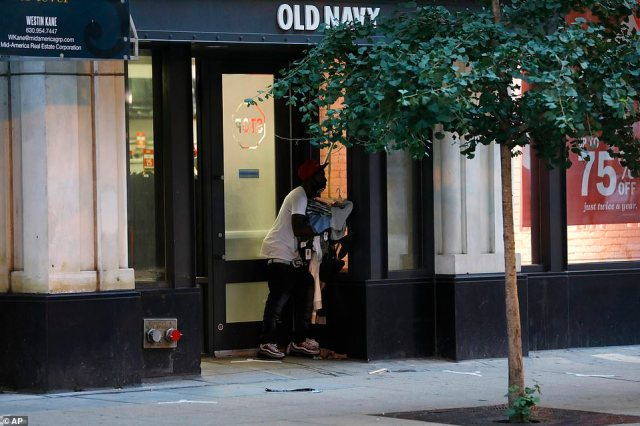 A person exits an Old Navy store in the Chicago Loop with an armful of clothing in the early morning of Monday, Aug. 10, 2020