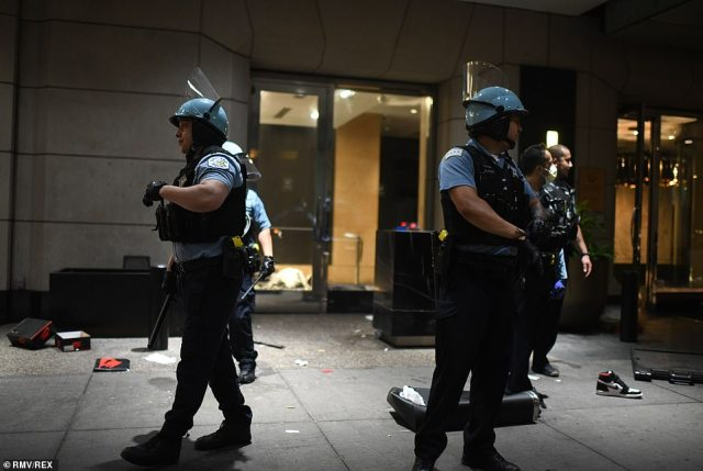 Chicago police officers in riot gear on Sunday night as they arrested the looters. More than 400 cops were dispatched to downtown Chicago