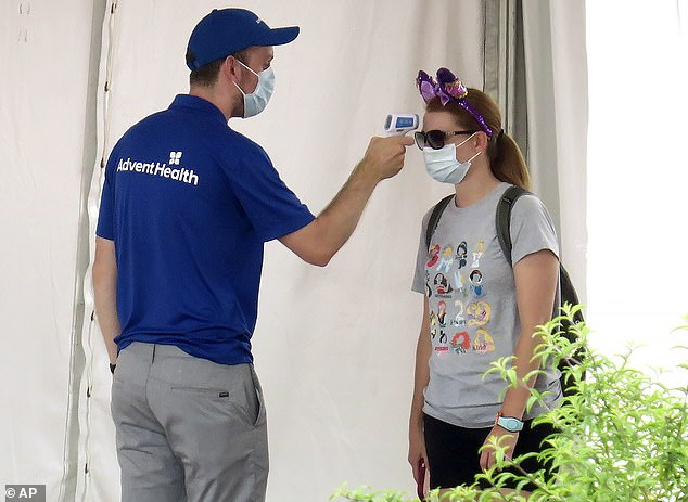 The Florida theme parks will rein in the amount of time guests can spend enjoying the magic from September 8, after it first reopened to the public back in July. Pictured a guest gets her temperature taken before entering the official reopening day of the Magic Kingdom