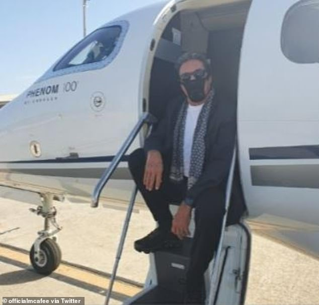 McAfee is seen posing in his thong mask on the steps of his private jet
