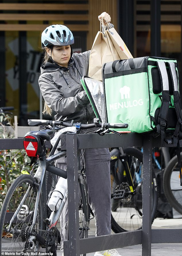 Food delivery services UberEats and Deliveroo are now bringing medication and groceries to customers' doors in Victoria (pictured, a delivery worker on July 6)