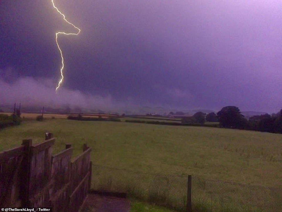 A fork of lightning strikes from a purple sky over the village of Llannefydd in Conwy, North Wales, last night