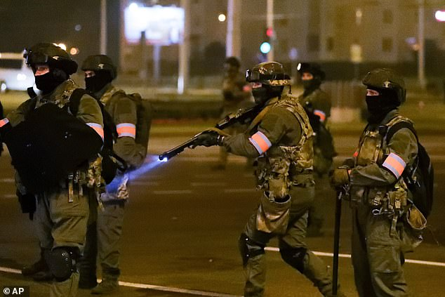 A police officer prepares to aim his weapon during the protests in the capital of Belarus last night after authoritarian leader Alexander Lukashenko claimed a sixth term