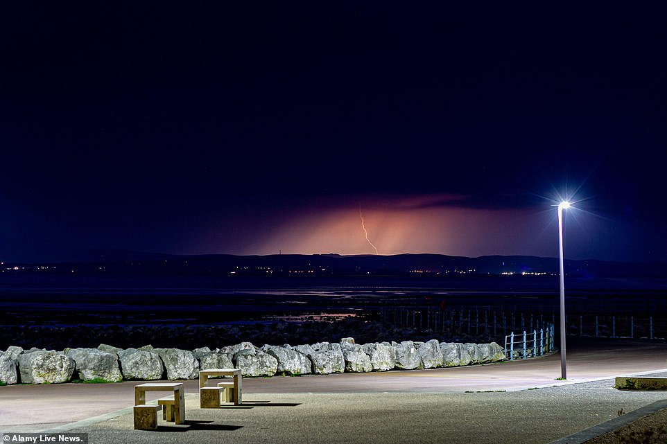 Thunder strikes near Morecambe in Lancashire overnight as thunderstorms and torrential downpours batter Britain