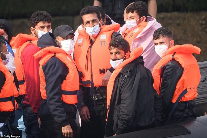 Migrants arrive in port aboard a Border Force vessel after being intercepted while crossing the English Channel from France in small boats