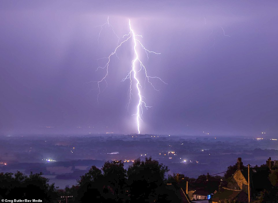 A lightning bolt cuts through the purple sky in Stoke-on-Trent yesterday amid thunderstorms in the Staffordshire area