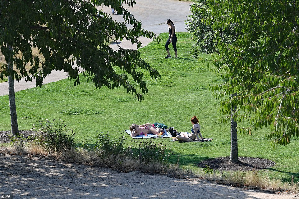 People enjoy the hot weather at Olympic Park in Stratford, East London, this afternoon as the heatwave continues