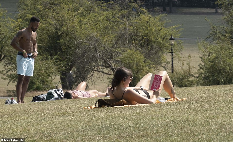 A woman reads a book as people enjoy the weather on Primrose Hill in North London this afternoon