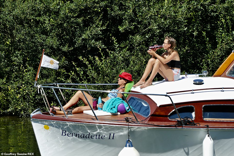 Boaters enjoy the warm weather at Goring-on-Thames in South Oxfordshire this afternoon as they sit on a boat