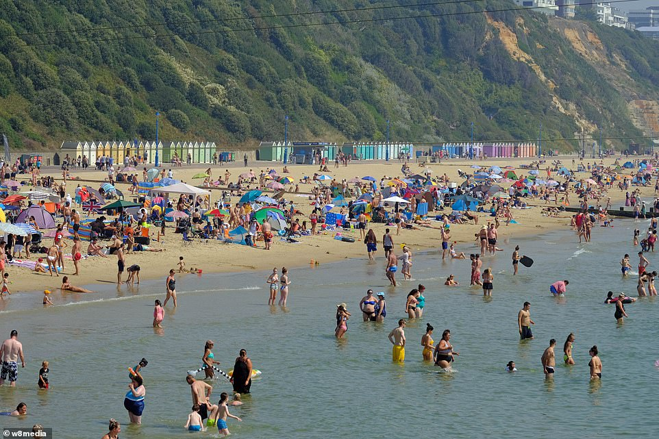 Daytrippers go into the water off Bournemouth beach in Dorset this afternoon as the heatwave continues for the country