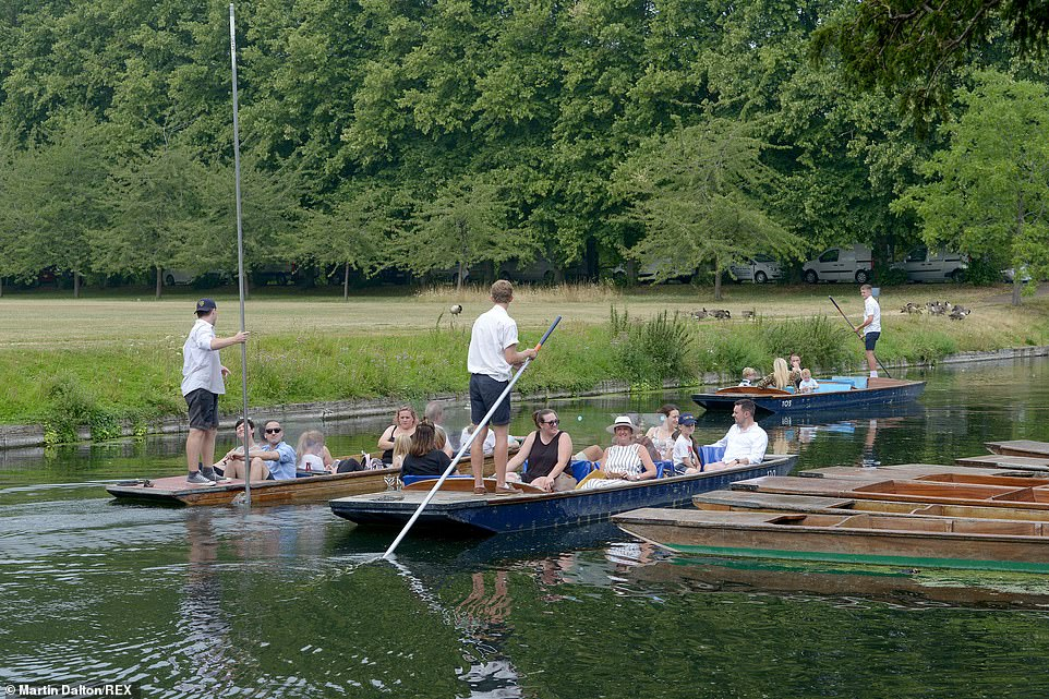 Visitors to Cambridge enjoy rides in punts on the Cambridge Backs on the River Cam this afternoon