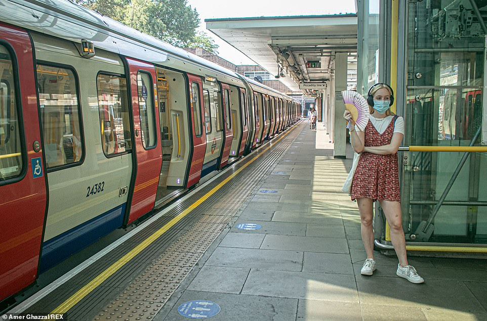 A passenger fans herself on a platform on the London Underground this afternoon amid the very hot weather in the capital