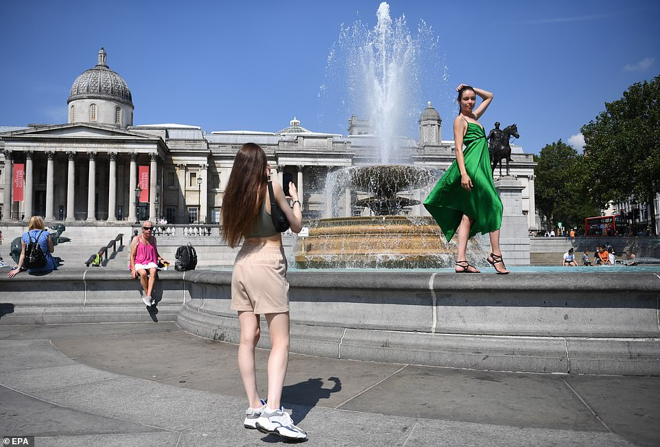 A woman poses for a friend's photograph in the sunshine at the fountains in Trafalgar Square in London this afternoon