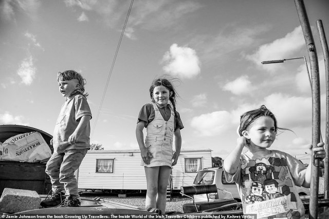 Three Irish traveller children stand in front of a caravan in this photograph captured by US-based photographer Jamie Johnson