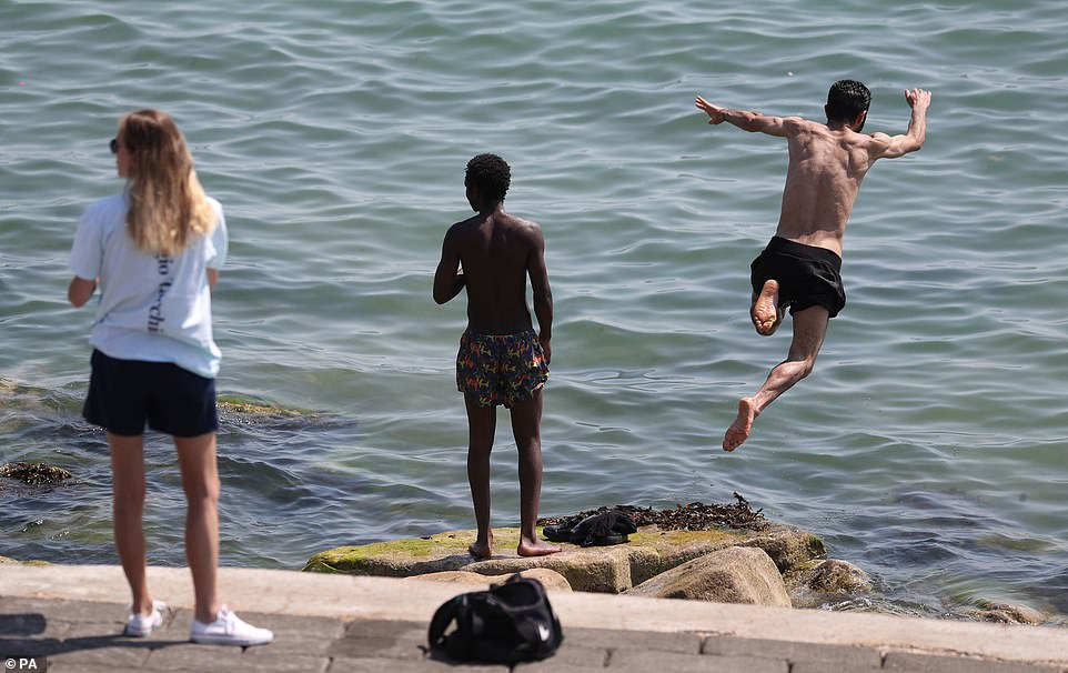 A person jumps into the sea as people enjoy the hot weather on Southsea beach in Hampshire this afternoon