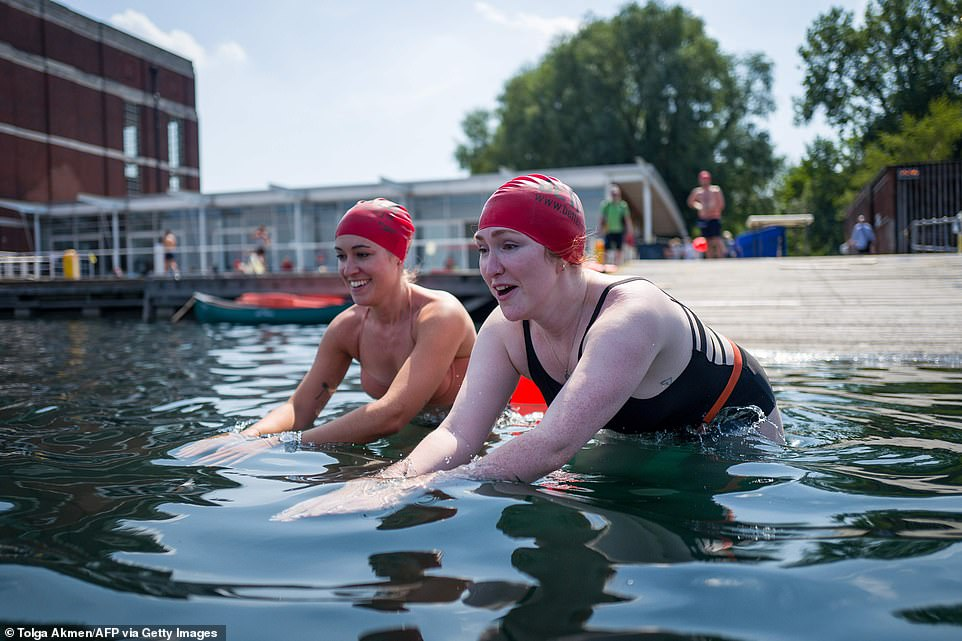People enjoy open water swimming at the West Reservoir Centre in North London this afternoon