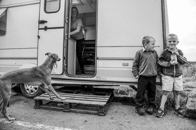 Two young Irish traveller boys and a greyhound stand outside a caravan in this photograph taken by US-based photographer Jamie Johnson