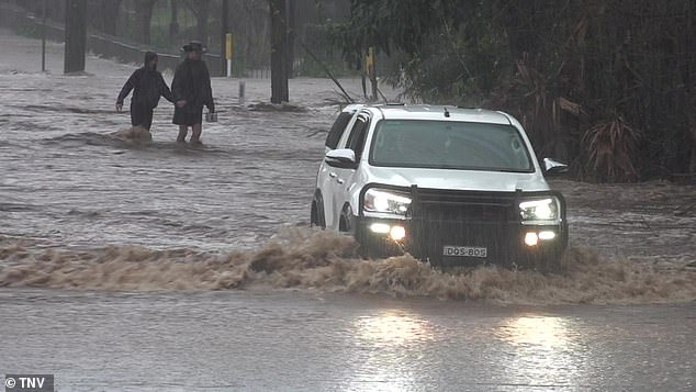Pictured: A car drives through flash flooding in Berry, south of Sydney, as wild weather wreaked havoc on the NSW South Coast over the weekend
