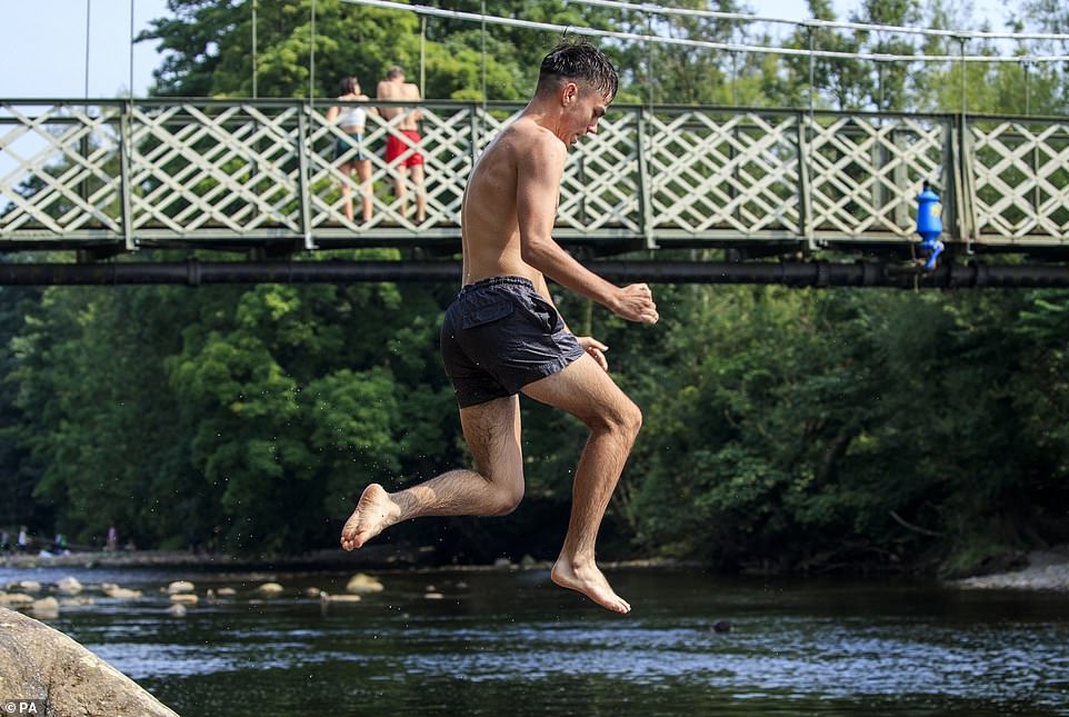 A man jumps from a rock into the River Wharfe near Ilkley in Yorkshire today as Britons enjoy the wave of warm weather
