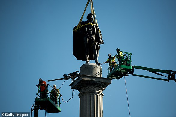 Workers use cherry pickers to help remove the John C. Calhoun statue atop a monument in Marion Square in Charleston, South Carolina in June