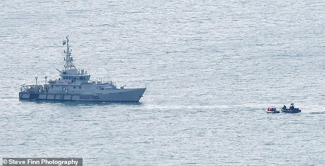 A migrant boat is pictured in the Channel beside a Border Force Seeker, August 11
