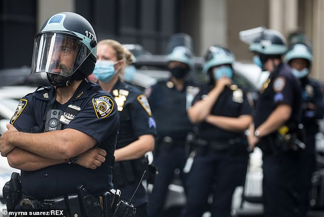 Officers from the New York Police Department prepare to confront protesters on August 7