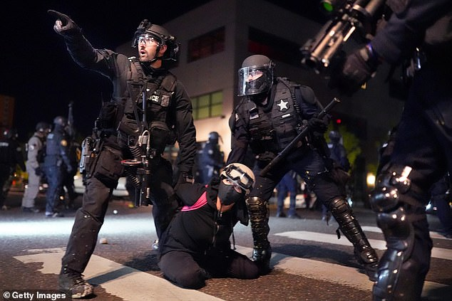 Police in Portland, Oregon arrest a protester in front of the precinct on Monday night