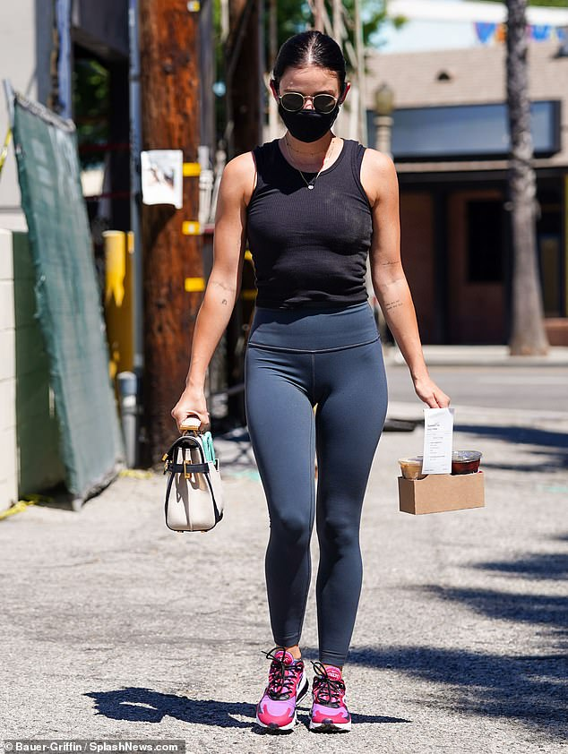 Out and about: The actress carried a white and black designer purse with gold clasp and wore a black cloth face mask as she picked up an order of drinks