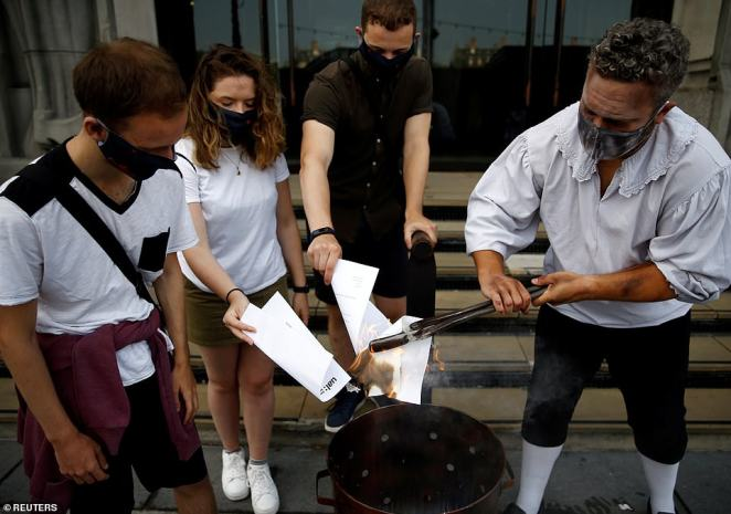Students burn their A-Level results at the London Dungeon today as pupils find out whether they have got a university place