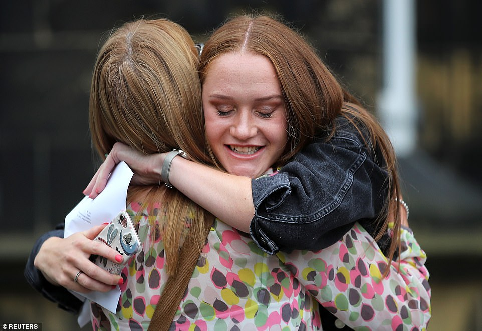 A sixth form student is embraced after receiving her A-level results at The Crossley Heath Grammar School in Halifax today