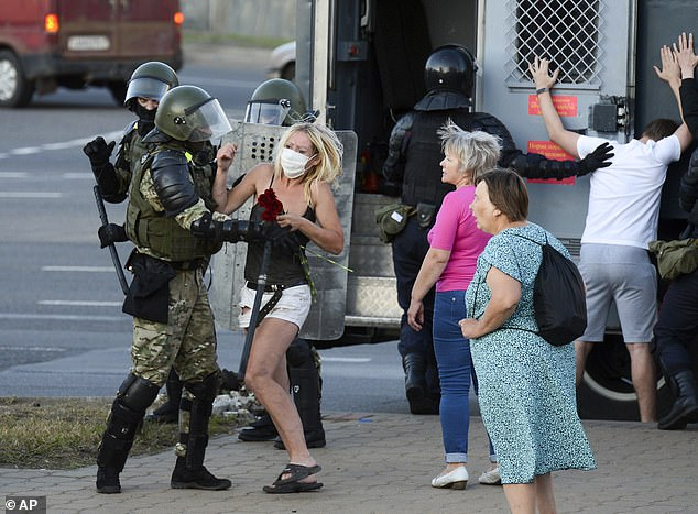A woman fights with a police officer as the other police officers detain an opposition supporter protesting the election results as protesters encounter aggressive police tactics in the capital of Minsk, Belarus, Tuesday