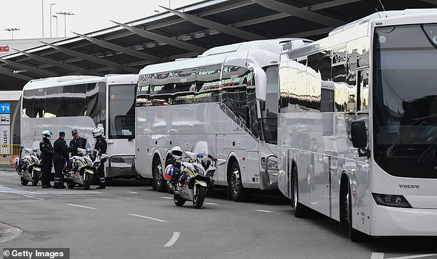 Coaches wait for their police motorbike escort to take passengers to hotel quarantine off a flight from Melbourne at Sydney International Airport on August 8