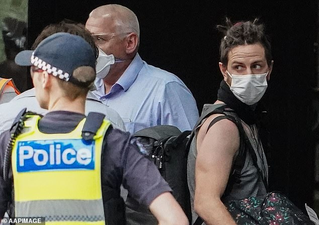 Recently arrived overseas travellers get off their bus and wait to check in at the hotel in Melbourne ahead of their quarantine